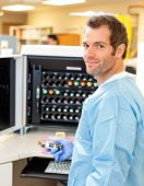 Side view portrait of lab tech holding sample by hematology analyzer