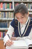 Student Doing Homework Near Bookshelf