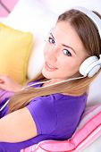 Conceptual image of  audio book. Beautiful girl with mobile phone and headphones.
