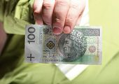 image of zloty  - Businessman holding polish money hundred zloty banknote - JPG