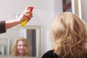 stock photo of hairspray  - Hairstylist With Hairspray And Female Client Blond Girl In Salon - JPG