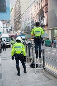 HONG KONG - NOVEMBER 14, 2012: Police men on the Queen's Road. Hong Kong has a unified police force - Hong Kong Police Force, it is considered one of the top notch organizations in world.