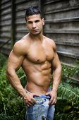 Muscular Young Latino Man Shirtless In Jeans In Front Of Concrete Wall