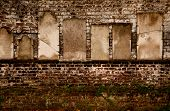 picture of headstones  - Headstones on a brick wall in a cemetary - JPG