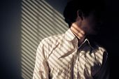 foto of blind man  - Young man next to a window with shadows being cast from the blinds - JPG