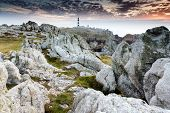 Unreal rocky coastline at dusk in the Ouessant island with the Creach lightohuse, Brittany, France