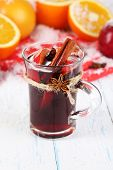 Fragrant mulled wine in glass on snow close-up
