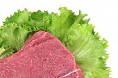 Raw beef meat with lettuce close up