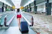 picture of escalator  - Young woman with a suitcase walking to escalator at airport - JPG
