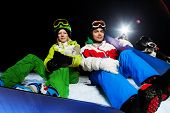 Two friends sitting with snowboards at night