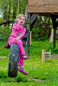 stock photo of tire swing  - yung girl sitting in tire swing - JPG