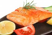 diet healthy food: hot grilled sea salmon fillet served on iron pan over wooden plate isolated on white background