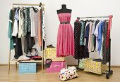 Dressing closet with polka dots clothes arranged on hangers and a dress on a mannequin.
