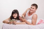 Happy Girl And Guy With Wad Of Money In Bed