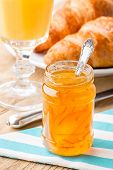 Orange jam with juice and croissants.
