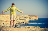 Man Traveler With Raised Hands Outdoor Sea And Rocks Coastal On Background Freedom Lifestyle Concept