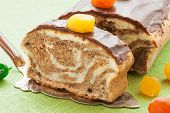 stock photo of pound cake  - Marble pound cake with chocolate glaze and caramelized fruits on kitchen table - JPG