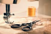 Antique scissors on fabric against vintage sewing machine threaded with cotton - vintage tone effect