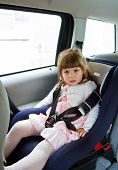 Little Cute Girl Sitting In The Car In Child Safety Seat And Smiling