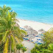 Coconut palms and thatched umbrellas at the beautiful Varadero beach in Cuba