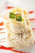 Dessert Maki Sushi - Roll with Banana and Cream Cheese inside. Pancake with Coconut outside. Served with Berries Sauce