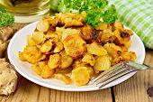Jerusalem artichokes fried with parsley in bowl on board