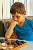 Pensive Boy During A Game Of Checkers