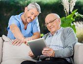 Happy male nurse helping senior man in using tablet computer at nursing home porch