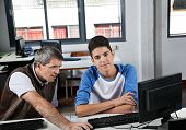 Portrait of teenage schoolboy with teacher using computer at desk in lab
