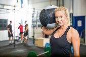Portrait of beautiful fit woman carrying medicine ball at crossfit gym