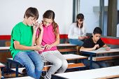 Teenage schoolchildren using mobilephone while listening music on desk in classroom