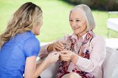 Granddaughter giving medicines to happy grandmother at nursing home porch