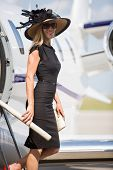 Side view portrait of wealthy woman smiling while disembarking private jet at airport terminal