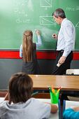 Rear view of little girl drawing geometric shapes on board while teacher assisting her in classroom