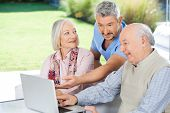 Male caretaker showing something to senior couple on laptop at nursing home