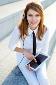 Contact center girl with hands free headset holding digital PC tablet