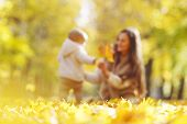 Beautiful young mother and her daughter in autumn park