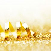 Curly golden gift ribbon on glitters background close-up