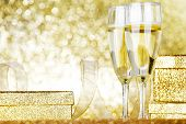 Champagne in glasses and gift box on golden background with twinkle lights