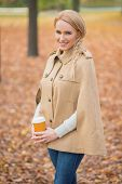 Close up Pretty Blond Woman in Fashionable Brown Autumn Attire Holding Cup of Coffee. Captured Outdoor While Looking at Camera.