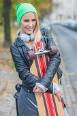Smiling Young Pretty Woman in Trendy Attire Embracing Skateboard at Street Side  Looking at Camera.