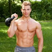 Close up Good Looking Topless Fit Man Carrying Weights Outdoor. Showing Six Packs Abs. Isolated on Nature Background.
