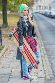 Trendy young woman carrying a skate board standing at the side of an urban street in warm winter clothing waiting for a lift