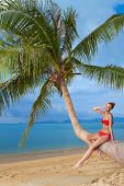Attractive woman sunbathing on a palm tree sitting on the trunk in her red bikini overlooking a sandy tropical beach and calm blue ocean
