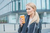 Attractive blond woman standing drinking takeaway coffee in a mug in warm winter clothes on an urban street