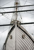 stock photo of tall ship  - Low Angle Detail of Tall Ship Bow or Stern with Mast in Background - JPG