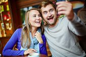 Ecstatic young couple taking their selfie