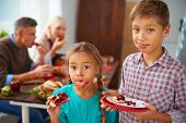 Portrait of funny kids eating sweet pie on background of their parents