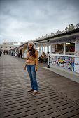 Full Length of Smiling Young Woman Wearing Warm Clothing Standing on Brighton Pier, England