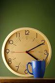 An analog clock and a blue coffee mug